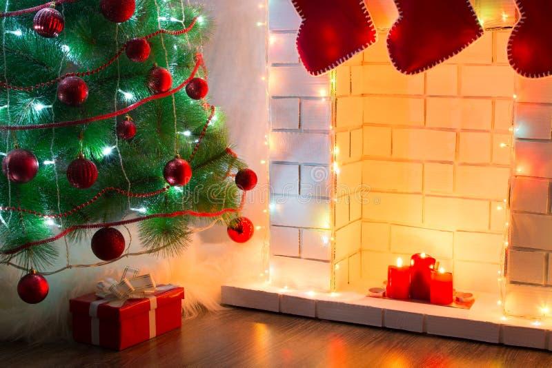 Härligt dekorerat träd med gåvor på golv nära spisen med varmt ljus av stearinljus royaltyfria foton