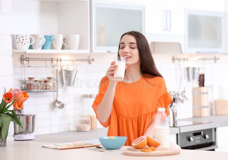 Härligt dricka för kvinna mjölkar i kök royaltyfri fotografi