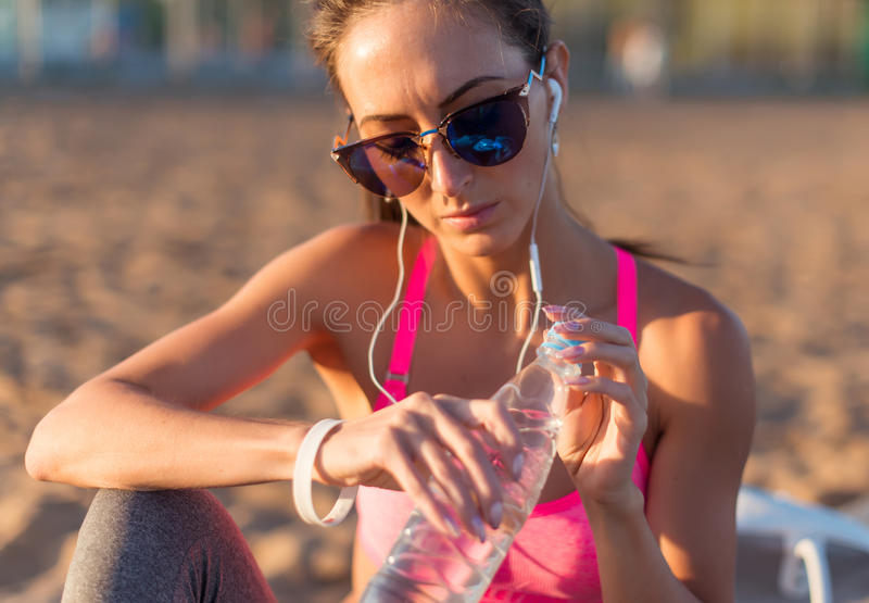 Härligt dricksvatten för konditionidrottsman nenkvinnan efter utarbetar att öva på solnedgångaftonsommar i den utomhus- stranden arkivfoto