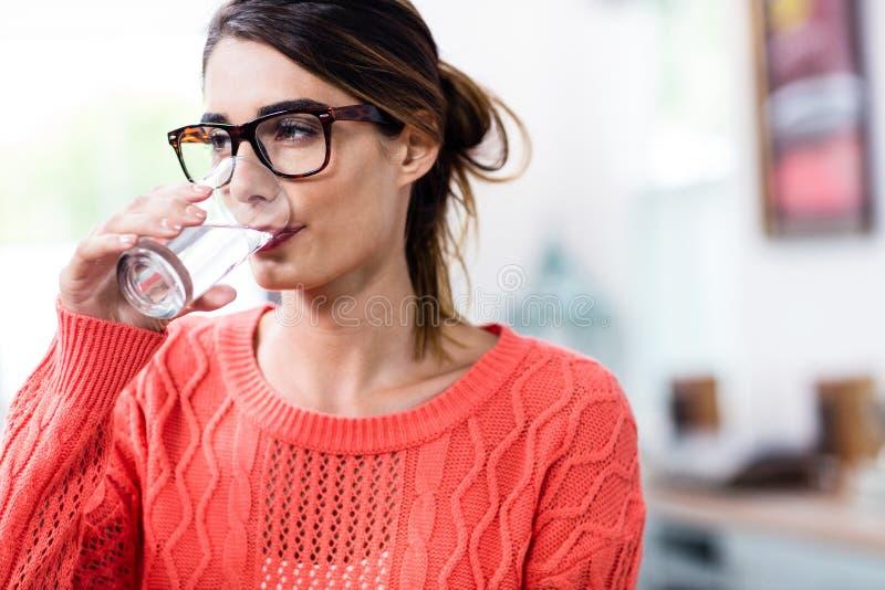 Härligt dricksvatten för ung kvinna i exponeringsglas royaltyfria bilder