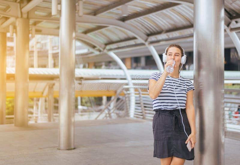 Härligt dricksvatten för ung kvinna och användahörlurar som lyssnar till musik i mittstaden arkivbilder
