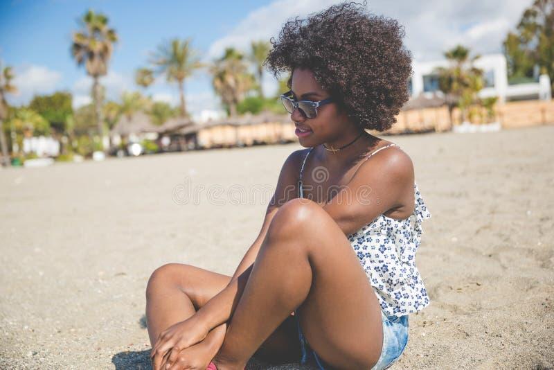Härligt eftertänksamt afro amerikanskt kvinnasammanträde på stranden fotografering för bildbyråer