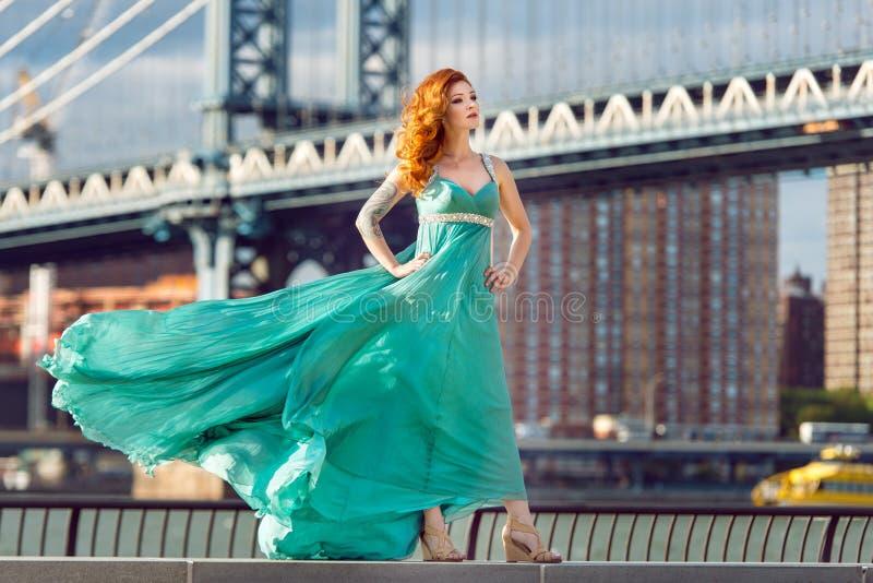 Härligt elegant rött haired kvinnaanseende nära den Manhattan bron i New York City som bär klänningen för lång gräsplan fotografering för bildbyråer