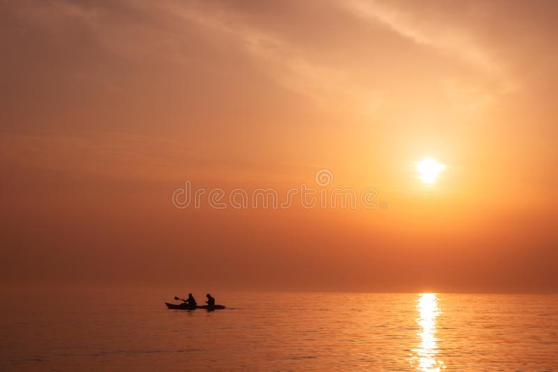 Härligt exotiskt solnedgånglandskap med konturn av kayaking män fotografering för bildbyråer