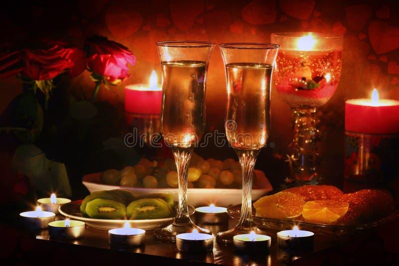Härligt exponeringsglas med rosa blad, ros-kronblad, steg kronblad på ett romantiskt datum med vin, stearinljus i levande ljus oc royaltyfria foton