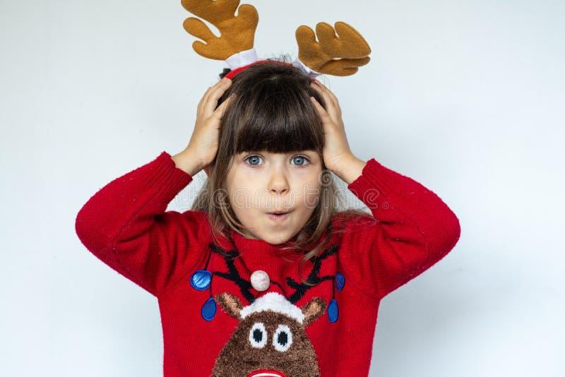 Härligt förvånat barn i den Santa Claus hatten, sinnesrörelser Rolig skratta barnstående nytt försäljningsår royaltyfri foto