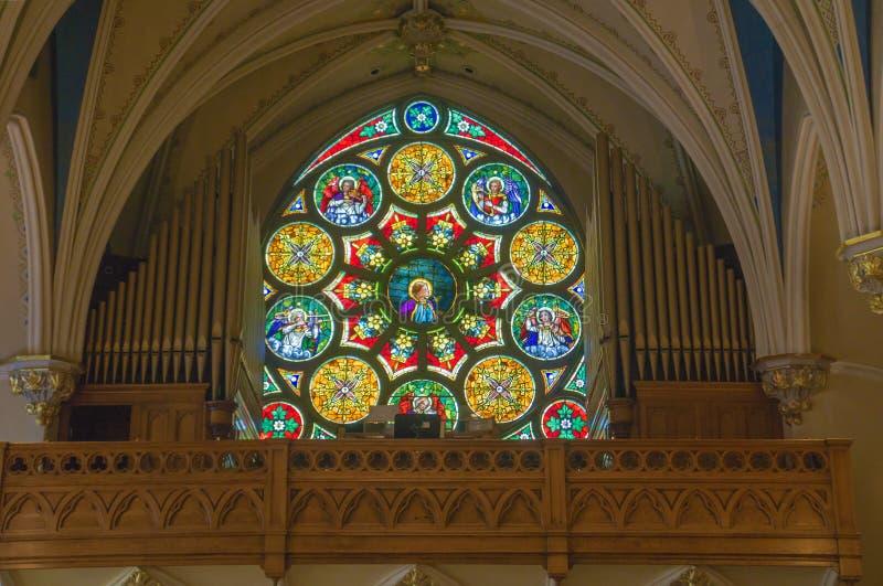 Härligt fläckexponeringsglasfönster på Sts Andrew katolsk kyrka fotografering för bildbyråer