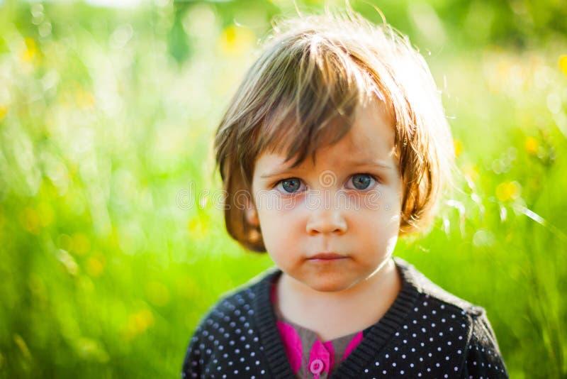 Härligt flickaanseende i gräs arkivfoto