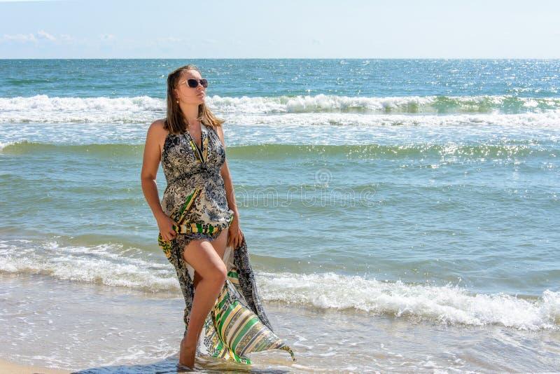 Härligt flickaanseende på stranden av Blacket Sea i solglasögon och klänningar royaltyfri bild