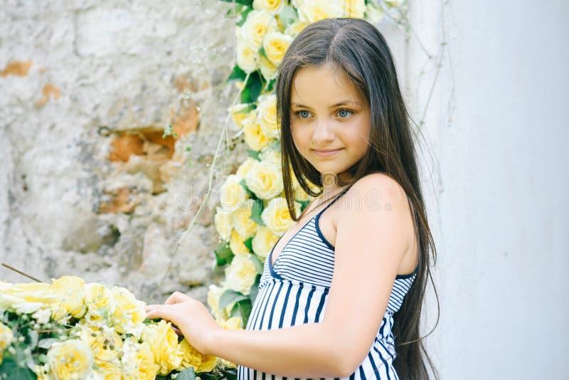 Härligt flickabarn i vårträdgård med gula rosor, blommor arkivfoton