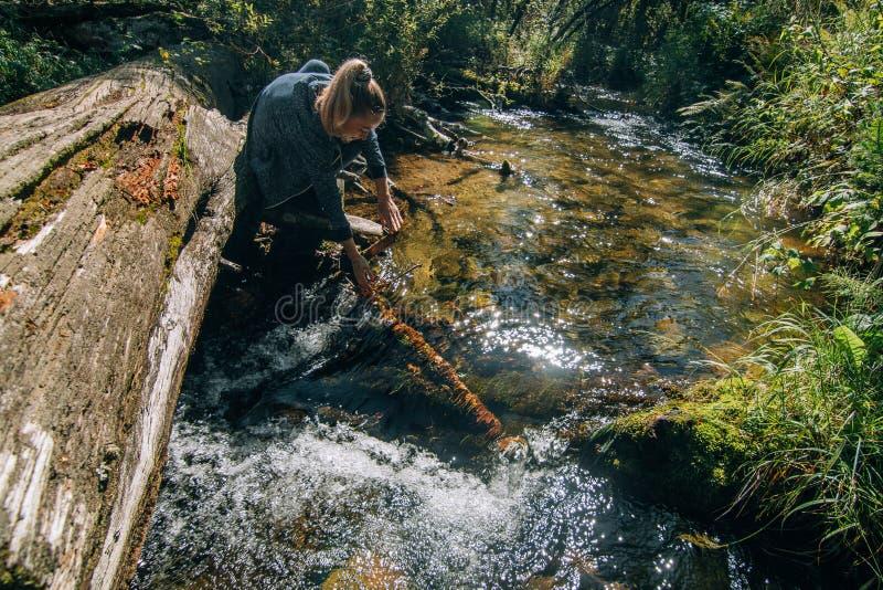 Härligt flickadricksvatten från floden på journal efter lopp Kvinnahandelsresanden i sommar passerar på träbron in arkivbild