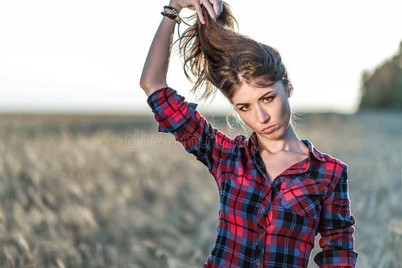 Härligt flickafält Sommar i natur Lyckliga håll hennes hår I aftonskjortan en brunettkvinna, närbildstående royaltyfria foton