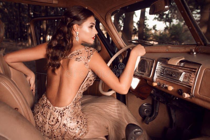 Härligt flickasammanträde bak hjulet av tappningbilar royaltyfri foto
