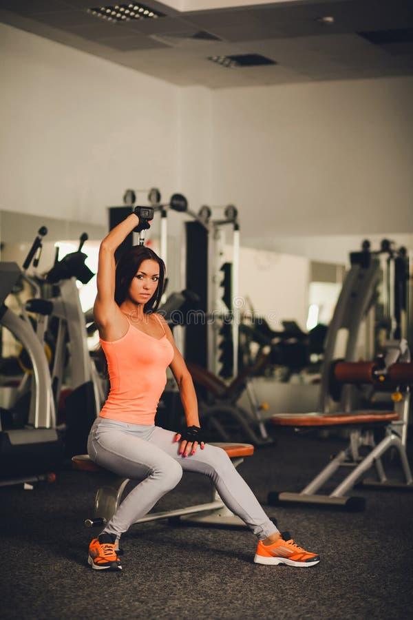 Härligt flickasammanträde i idrottshallen och gör övningar royaltyfri foto