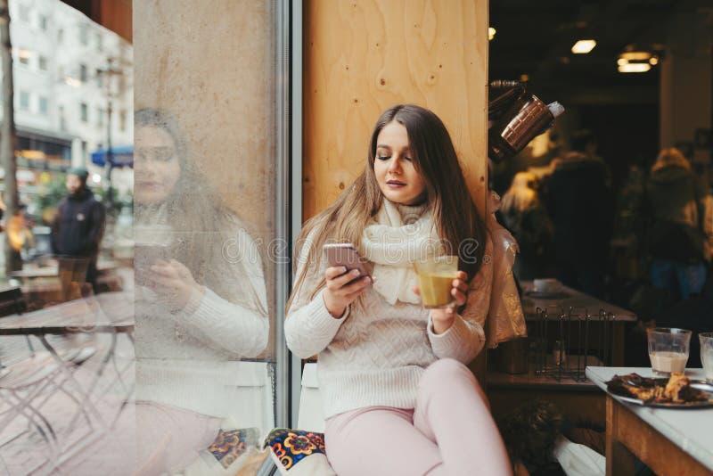 Härligt flickasammanträde på fönstret i kafé fotografering för bildbyråer