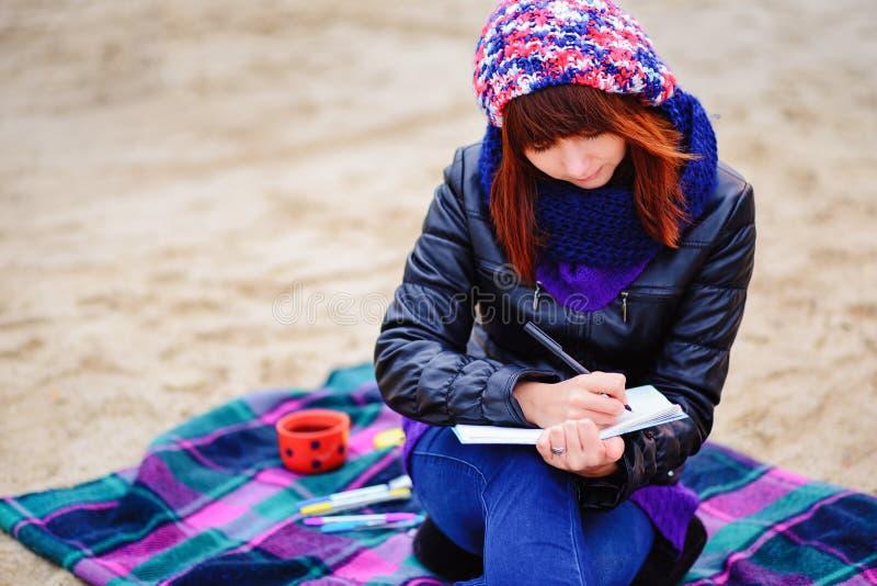 Härligt flickasammanträde på stranden och har rekord i en noteboo arkivfoto