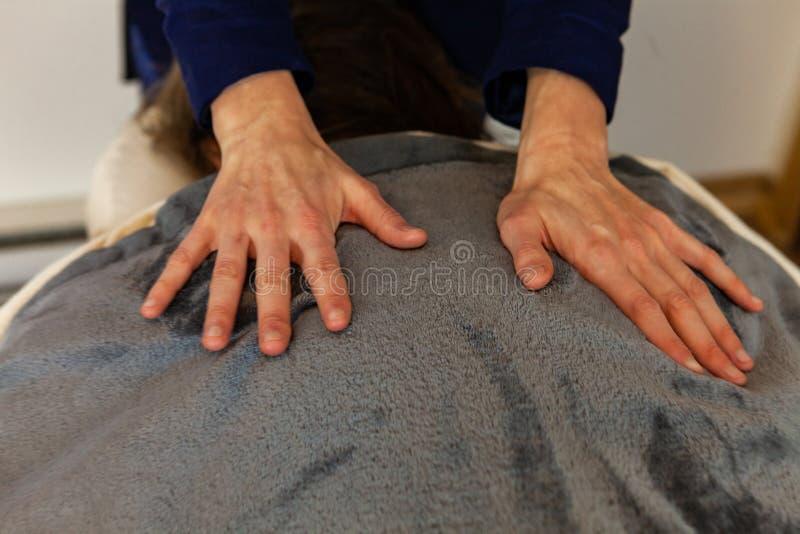 Härligt foto av en kvinnas händer som ger en djup silkespappermassage royaltyfri bild
