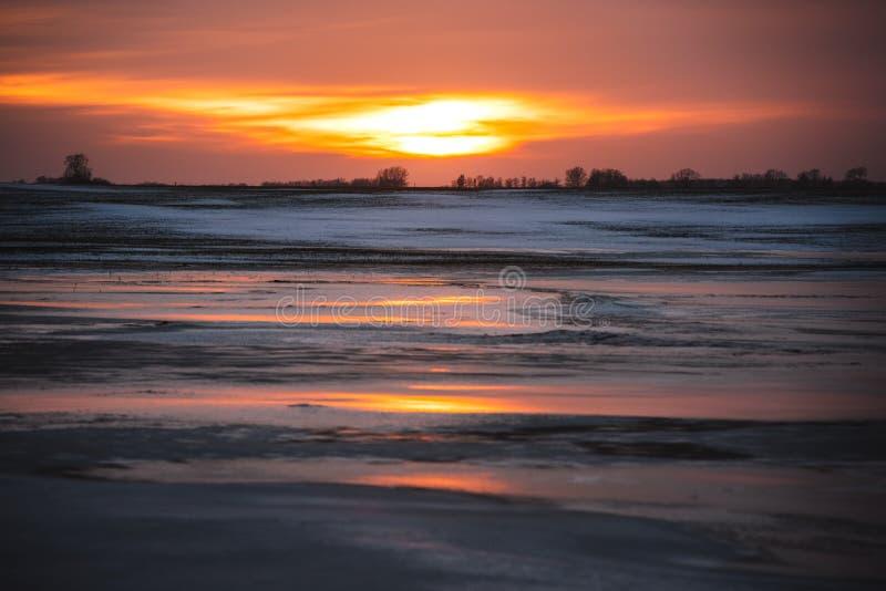 Härligt frostigt solnedgånglandskap och orange reflexion på is royaltyfri fotografi