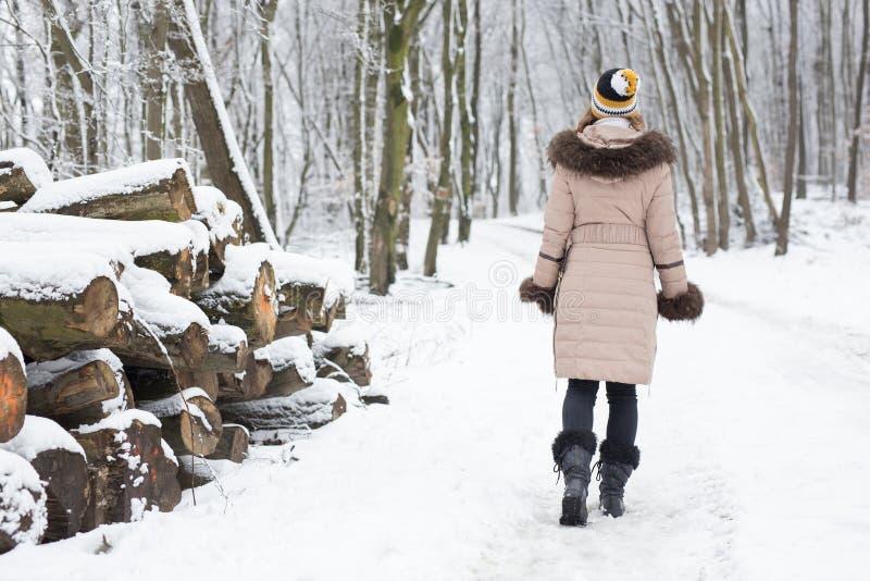Härligt gå för ung kvinna som är lyckligt i det mest forrest på en vinter D arkivfoto
