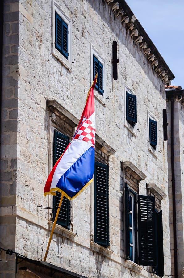 Härligt gammalt hus med den kroatiska flaggan på den huvudsakliga gå gatan i den gamla staden av Dubrovnik royaltyfri foto