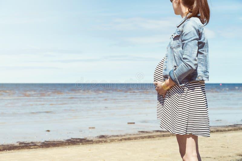 Härligt gravid kvinnaanseende på stranden Gravid kvinna som tar en gå vid stranden royaltyfria foton