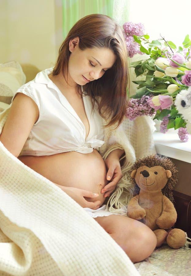 Härligt gravid kvinnasammanträde på soffan. royaltyfri foto