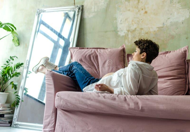 Härligt gravid kvinnasammanträde på soffan hemma royaltyfri bild