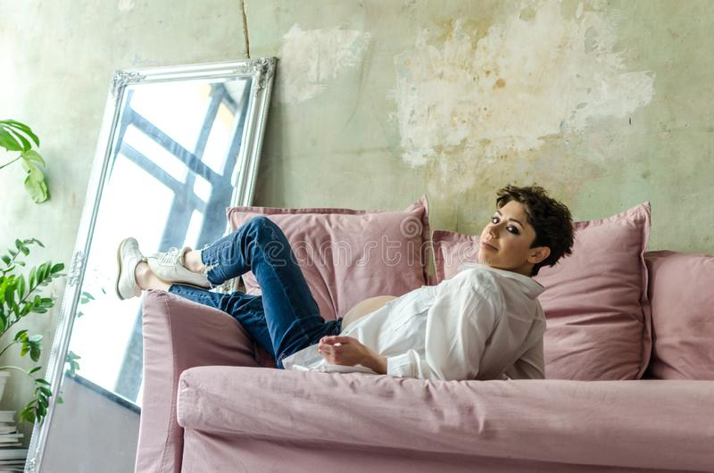 Härligt gravid kvinnasammanträde på soffan hemma arkivfoto
