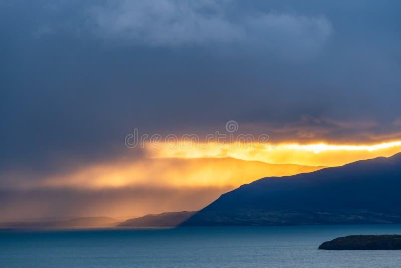 Härligt guld- orange ljus av sollöneförhöjningen över berget med den djupblå sjön i morgonen, i att regna molnet i Torres del arkivfoto