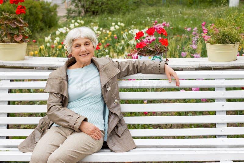 Härligt gulligt äldre kvinnasammanträde på en parkerabänk med blommor fotografering för bildbyråer