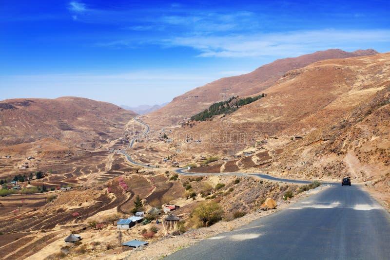 Härligt höglands- dallandskap, landskappanoramautsikt, väg och by i Drakensberg berg, Lesotho, sydliga Afrika royaltyfri fotografi