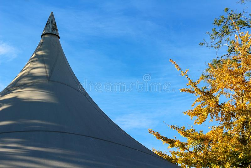 Härligt höstlandskap med det vita taket för händelsestort festtälttält mot blå himmel arkivbild