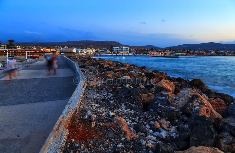 Härligt hav med mjukt ljus för afton av solnedgången mot molnig himmel med den kust- linjen med stenar och promenadbanan royaltyfria bilder