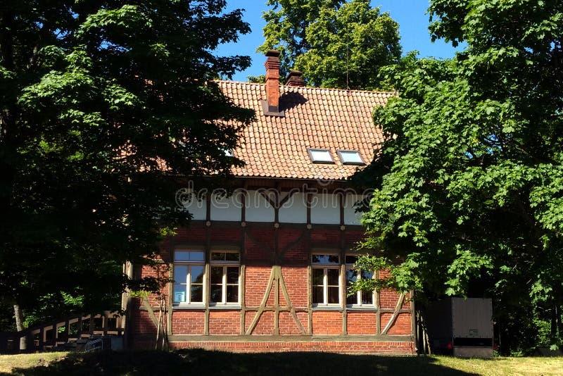 Härligt hus som omges av grönska på en klar solig dag royaltyfria foton