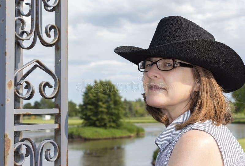 Härligt huvudskott av bärande exponeringsglas för en kvinna och en svart cowboyhatt arkivfoton
