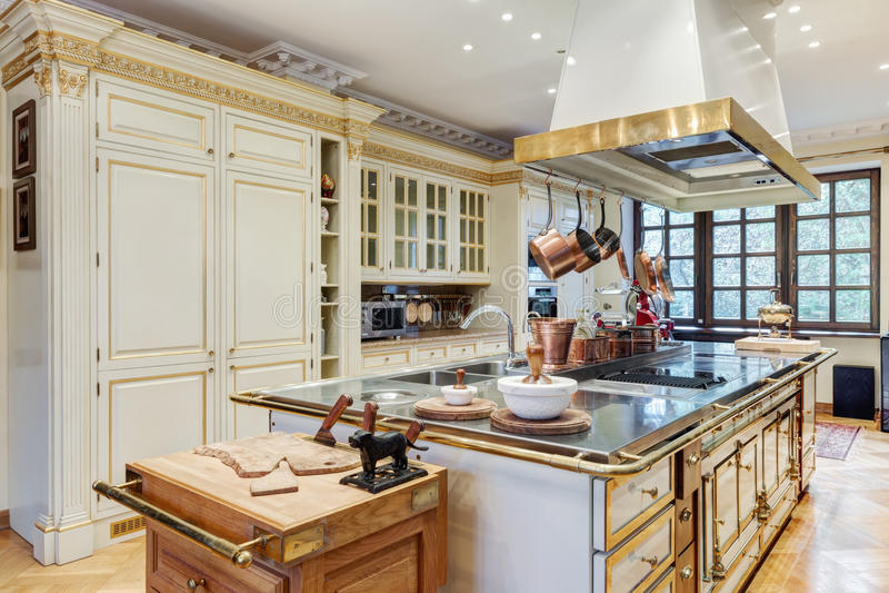 Härligt kök med ön och med kopparredskap royaltyfria bilder