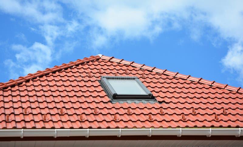 Härligt keramiskt belagt med tegel rött hustak med takavloppsrännan, lofttakfönsterfönstret och kopieringsutrymme arkivfoto