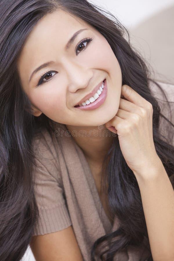 Härligt kinesiskt orientaliskt asiatiskt le för kvinna royaltyfri bild