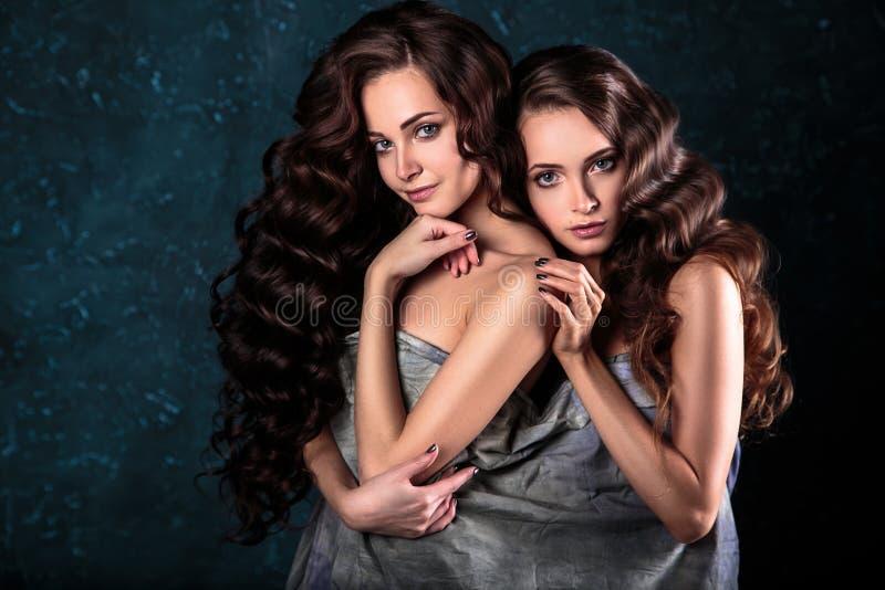 Härligt kopplar samman unga kvinnor med naturlig smink- och hårstil som poserar naket dolt med den gråa torkduken, closeupstående royaltyfria bilder