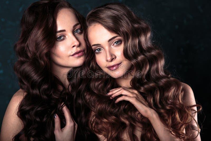 Härligt kopplar samman unga kvinnor med naturlig smink- och hårstil som poserar naket dolt med den gråa torkduken, closeupstående fotografering för bildbyråer