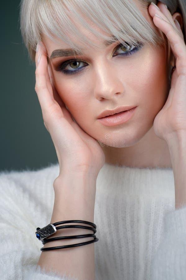 Härligt kort hår Skönhetkvinna med lyxigt rakt vitt hår på en grå bakgrund Härliga blonda modellflickahandlag arkivfoto