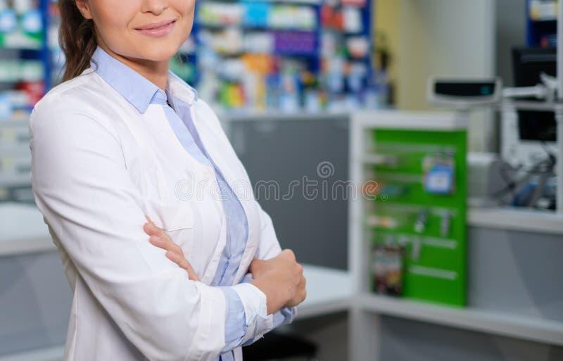 Härligt kvinnaapotekareanseende på hennes arbetsplats i apotek royaltyfria bilder