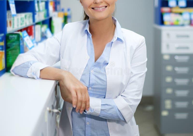 Härligt kvinnaapotekareanseende på hennes arbetsplats i apotek royaltyfria foton