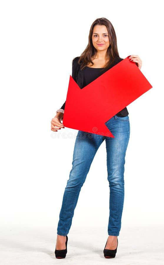 Härligt kvinnainnehav som peka för pil besegrar arkivfoto