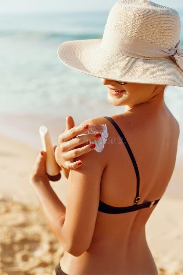 Härligt kvinnaleende som applicerar solkräm på skuldra Skincare Kroppsolskydd sunscreen Hudskydd och dermatologi arkivbild