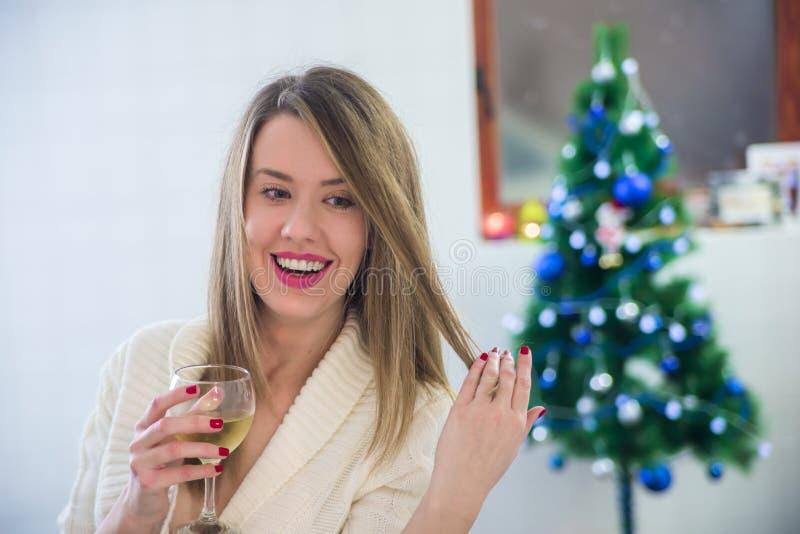 Härligt kvinnasammanträde bredvid julgranen som tycker om exponeringsglas av vin stående av den unga le kvinnan i dekorerad varda fotografering för bildbyråer