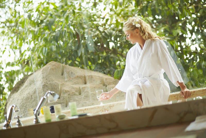 Härligt kvinnasammanträde i badrock i badrum i lyxigt hotell arkivfoton