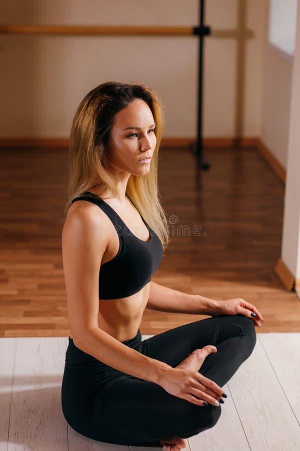 Härligt kvinnasammanträde i lotusblomma poserar och meditera på yogastudion royaltyfri foto