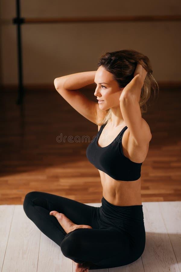 Härligt kvinnasammanträde i lotusblomma poserar och meditera på yogastudion royaltyfri bild