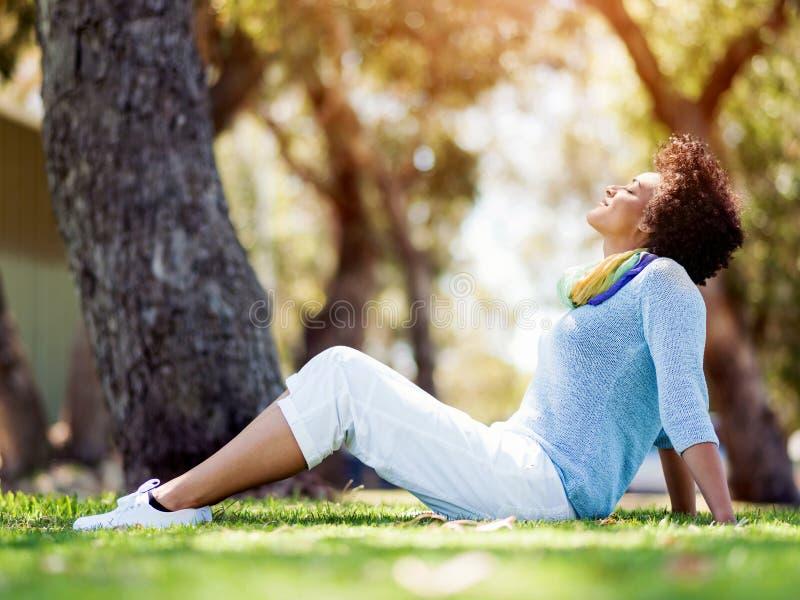 Härligt kvinnasammanträde i sommar parkerar royaltyfri bild